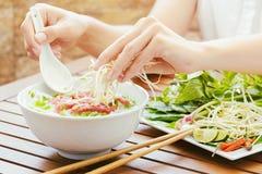少妇洒新芽对在越南咖啡馆的Pho Bo 库存照片