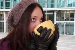 少妇水杯茶在冬天户外在镇里 免版税库存照片