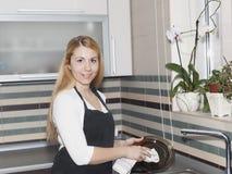 少妇洗涤的盘在厨房里 免版税图库摄影