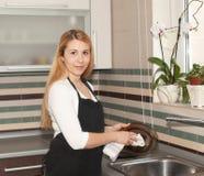 少妇洗涤的盘在厨房里 免版税库存图片