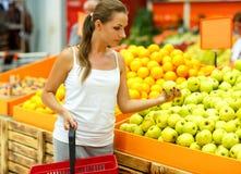 少妇购物在果子的部门的一个超级市场 免版税库存照片