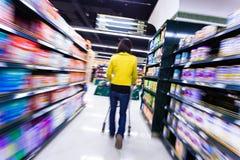 少妇购物在超级市场,行动迷离 库存照片