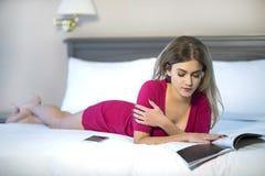 少妇读的放松,当读在床上时 免版税库存照片