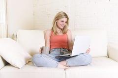 少妇说谎舒适在家庭沙发使用便携式计算机微笑的互联网愉快 免版税库存图片