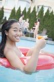 少妇画象拿着饮料和坐在水池的一支可膨胀的管 免版税库存图片