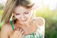 少妇画象有桃红色玫瑰的在她的在sunshi的头发 免版税库存图片