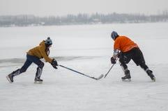少年与成熟人的女孩战斗为顽童,当使用hokey在一条冻河Dnipro在乌克兰时 免版税库存照片