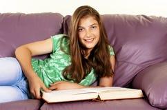 少年书女孩位于的读取的沙发 免版税库存图片
