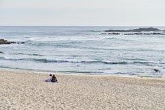 少年供以座位单独谈话在海滩 免版税库存图片