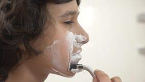 少年刮第一次,申请的十几岁的男孩刮泡沫,skincare,奶油,面孔,特写镜头 股票录像