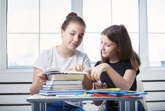 少年十几岁学生坐在与书st的桌上 免版税库存图片