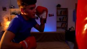 少年向体育求助,猛击的把装箱的袋子在他的屋子里,阴影拳击 库存照片