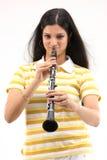 少年吹的单簧管的女孩 免版税库存照片