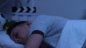 少年在智能手机的读书新闻在床上直到很晚在晚上,小配件瘾 股票录像