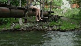 少年坐在山河的一个狭窄的木桥 野营和冒险概念 股票录像