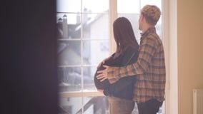 少年夫妇在家一起 爱抚他怀孕的女朋友的腹部的年轻人站立在她后 A 股票视频
