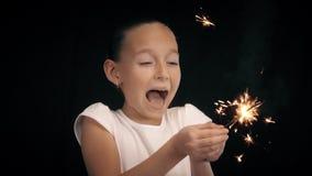 少年女孩保留在烧孟加拉光和愉快笑与火花的手在暗室 股票视频