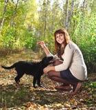 少年女孩和黑色拉布拉多猎犬小狗 免版税库存照片