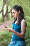 少年女孩是松弛在公园和使用巧妙的电话 她i 免版税库存照片