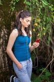 少年女孩是松弛在公园和使用巧妙的电话 她i 库存照片
