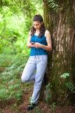 少年女孩是松弛在公园和使用巧妙的电话 她i 图库摄影