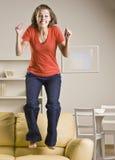 少年女孩跳的沙发 免版税图库摄影