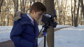 少年学会在冬天公园拍摄与专业摄影机的影片 影视素材
