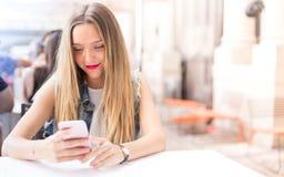 少年室外与她的手机 免版税库存图片