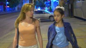 少年容忍的母亲和女儿的画象穿过晚上城市漫步 一个温暖的夏天晚上 股票视频