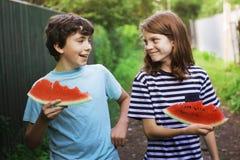 少年微笑的男朋友举行西瓜切片吃 免版税库存照片