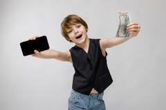 少年拿着一个电话在一只手上和在另一金钱 有金发和黑眼睛的迷人的少年 少年是 免版税库存照片
