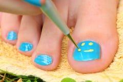 少年有搪瓷laque刷子修脚的女孩手她的脚趾脚 库存照片