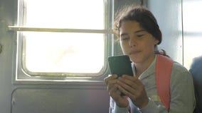 少年有背包的女孩旅客坐袋子背包在汽车的窗口有智能手机的 旅行路轨 股票录像