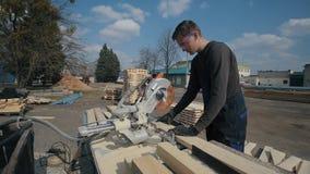 少年木匠工作者佩带制服和使用木切割机 宽看法 股票录像