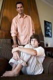 少年父亲家庭沙发的儿子 免版税库存图片