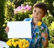 少年男孩举行与玫瑰和flox的白纸板料开花 图库摄影