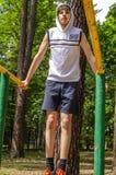 少年男孩做着在双杠的锻炼 库存照片
