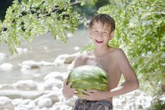 少年男孩在手上的拿着新鲜的绿色西瓜 库存照片
