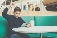 少年男孩坐在咖啡馆桌,在智能手机的戏剧流动比赛上 男孩坐用他的手,胜利,赏金 库存照片