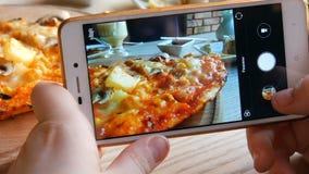 少年男孩拍食物照片在智能手机的 在餐馆桌上的意大利薄饼 股票录像