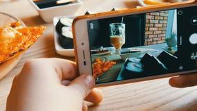 少年男孩拍食物照片在智能手机的 在餐馆桌上的意大利薄饼 影视素材