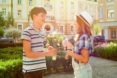 少年男孩祝贺有花花束的女孩户外 库存照片