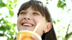 少年的女孩在公园喝着秸杆鸡尾酒和微笑着 特写镜头 股票视频