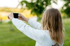 少年的女孩 夏天本质上 在他的手上拿着一个智能手机 自然拍在街道的照片 免版税库存照片