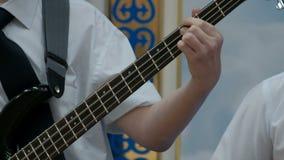 少年的手指夹紧在吉他的苦恼的串 白色衬衫的一个年轻低音吉他球员 股票视频