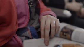 少年读书编目在候诊室在机场,翻转页,特写镜头 股票视频
