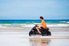 少年骑马在海滩的方形字体自行车 图库摄影