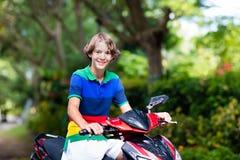 少年骑马滑行车 摩托车的男孩 免版税库存照片