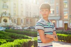 少年13, 14岁,有横渡的胳膊的男孩,都市背景室外画象  免版税库存图片