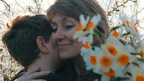 少年` s儿子献一个成人中年妈妈白色黄水仙花束在一棵开花的树的背景的 影视素材